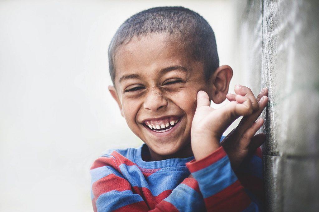 Imagem de uma criança africana vestindo uma blusa de frio listrada nas cores azul claro e vermelho. Ela está muito feliz e sorrindo. Imagem de Pexels por Pixabay.