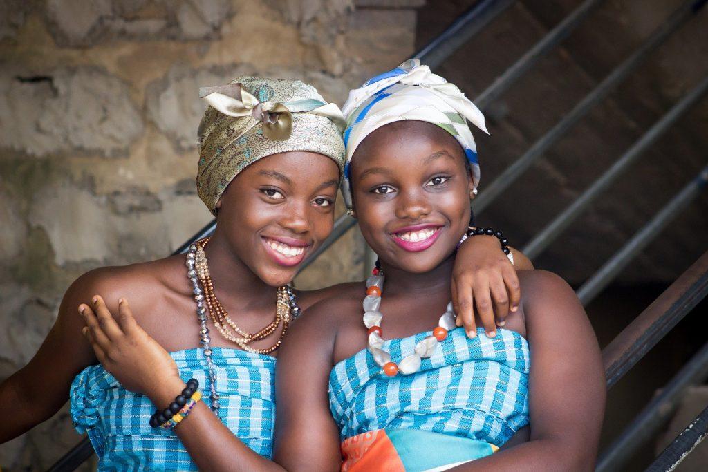 Duas lindas mulheres negras sorrindo. Elas vestem um vestido listrado azul e branco, colares, pulseiras e turbantes. Imagem de Jason Sackey por Pixabay.
