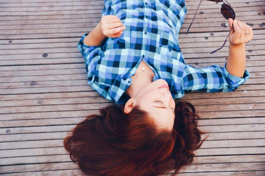 Mulher deitada em um piso de madeira segurando um óculos de sol