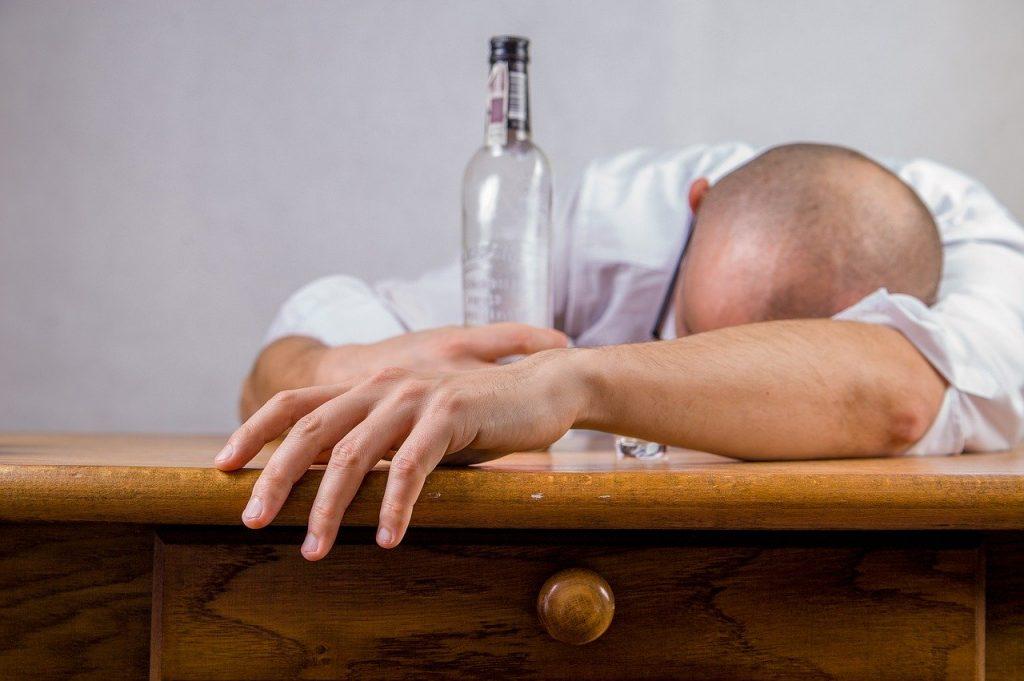 Homem com a cabeça deitada em uma escrivaninha de madeira. Seu braço esquerdo está esticado até sua mão sair da escrivaninha, enquanto sua mão direita segura uma garrafa de vidro vazia, apoiada na escrivaninha.