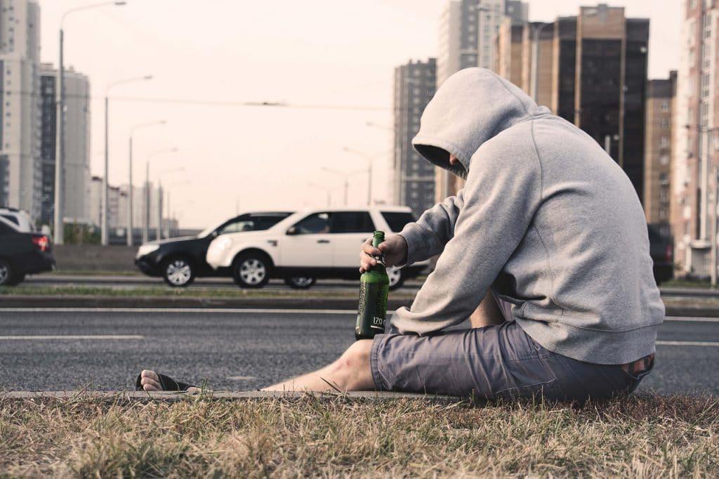 Homem vestindo moletom com capuz e bermuda, sentado na sarjeta, segurando uma garrafa de cerveja.