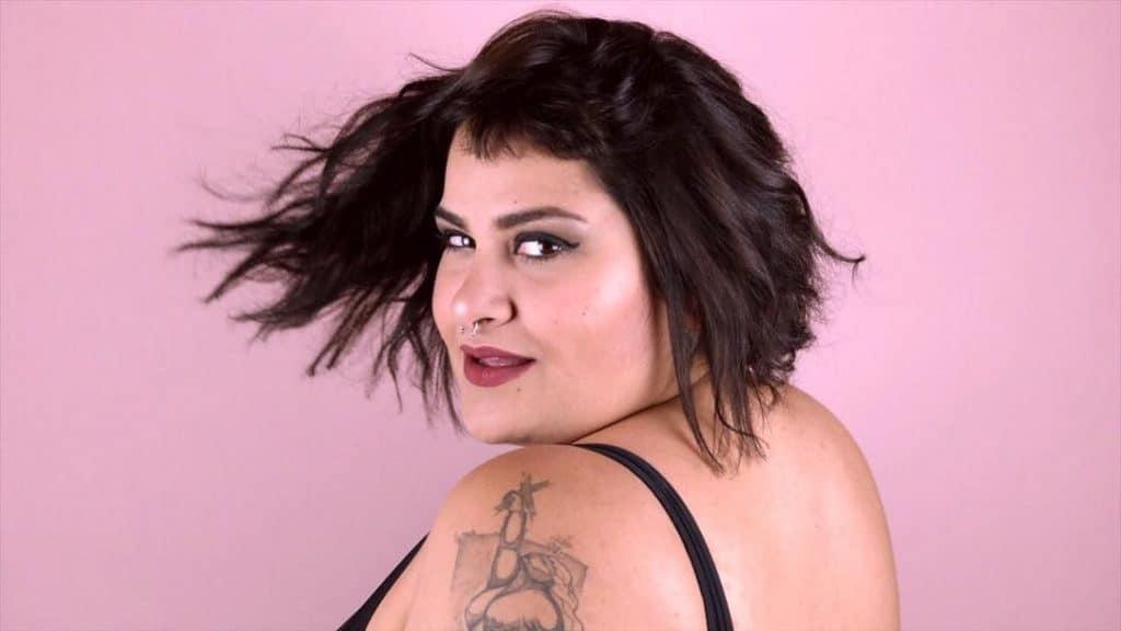 Fotografia de Alexandra Gurgel, de costas, com o rosto virado para a câmera.