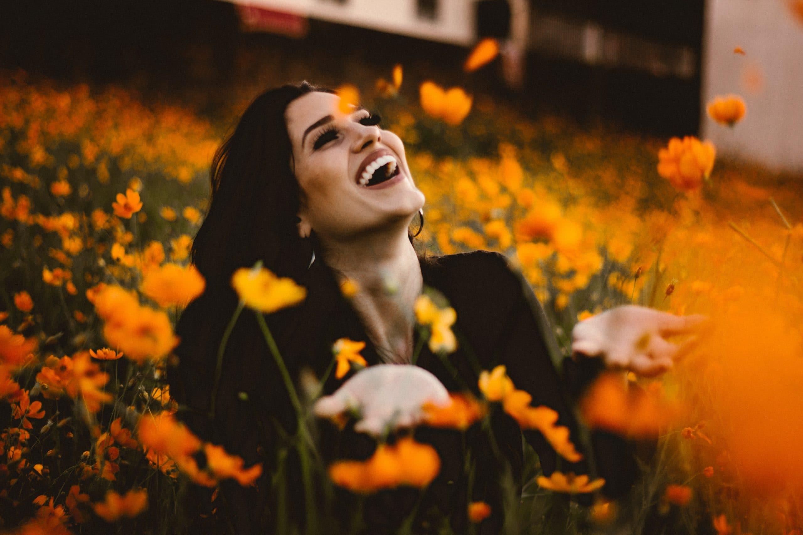 Mulher sorrindo em campo de flores.