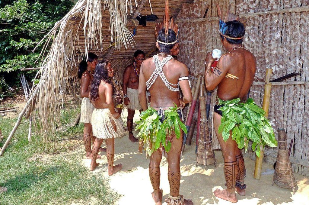 Índios em frente a uma oca, usando vestes feitas de folhas., de costas para a câmera.