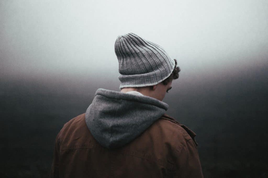 Homem de frente para um fundo escuro