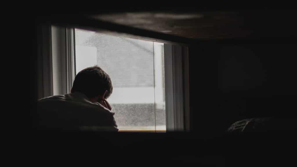 Homem olhando o lado de fora pela janela