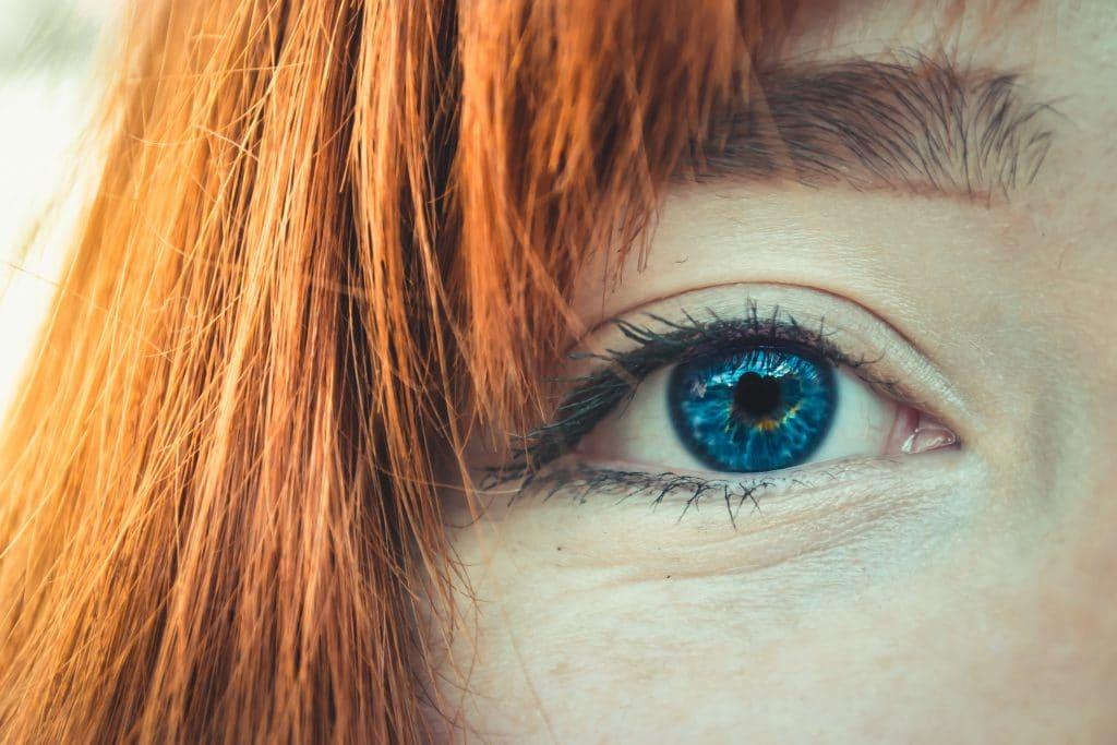 Olho visto de perto com cabelos ruivos na lateral do rosto