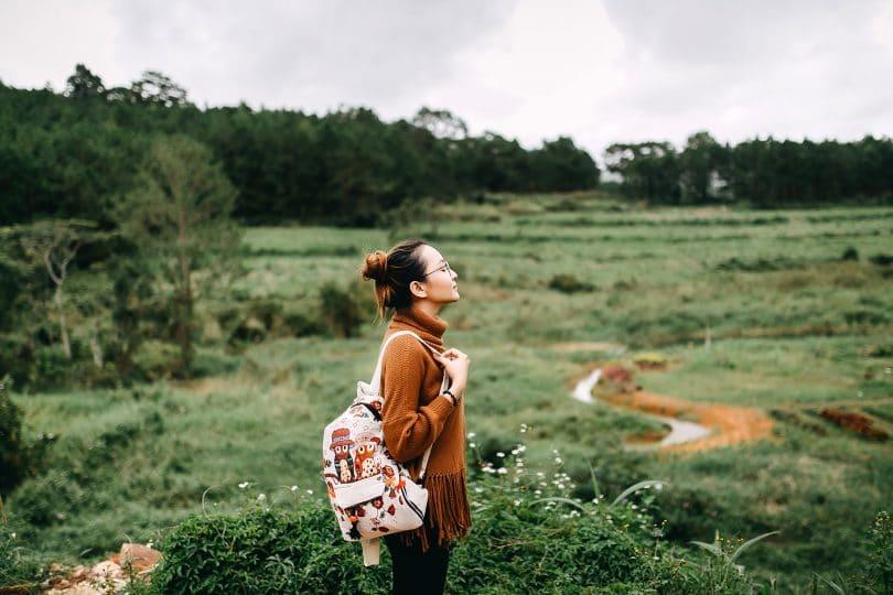 Mulher em paisagem com natureza olhando para cima.