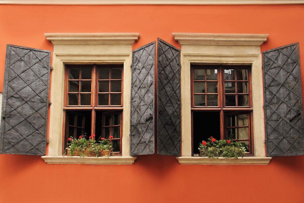 Parede externa de um quarto pintada na cor laranja. Temos duas janelas grandes de madeira e cada uma delas possui um floreira.