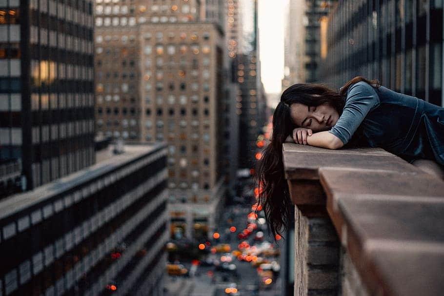 Mulher repousando a cabeça em seus braços, no parapeito de um prédio em uma cidade grande.