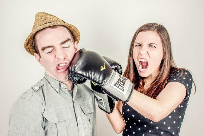 Casal de homem e mulher simulando uma briga. Ela usa uma luva de boxe e está simulando um soco no rosto do homem.