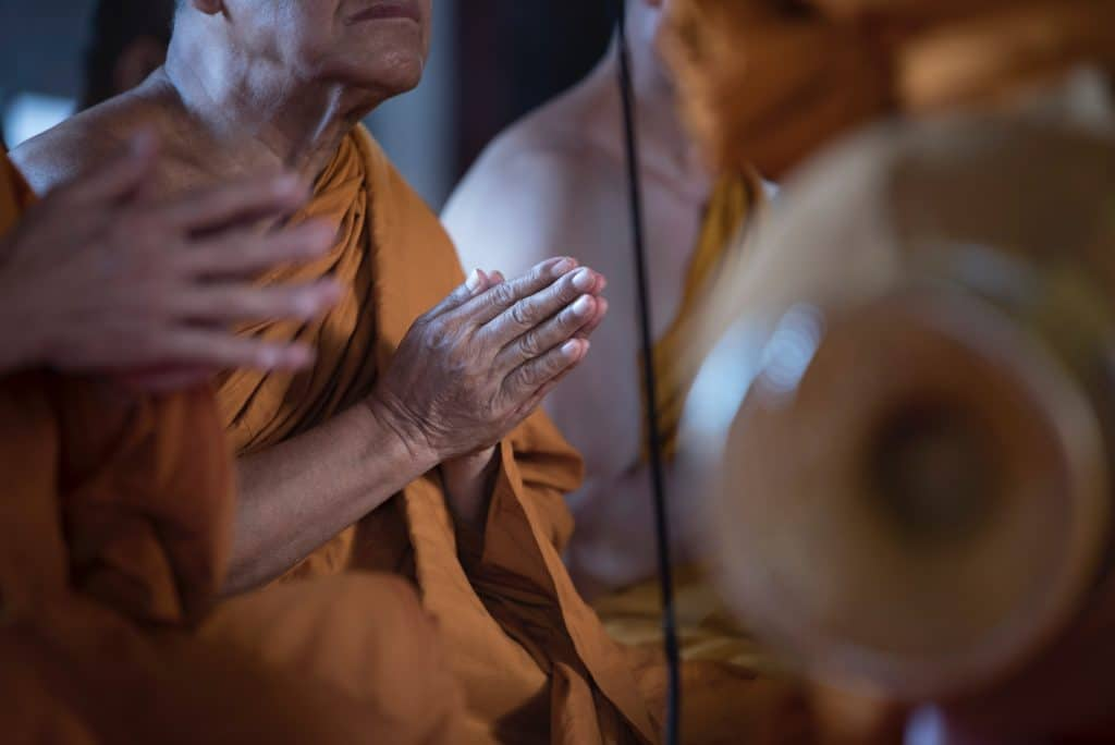 Monge budista com as mãos unidas, em oração.