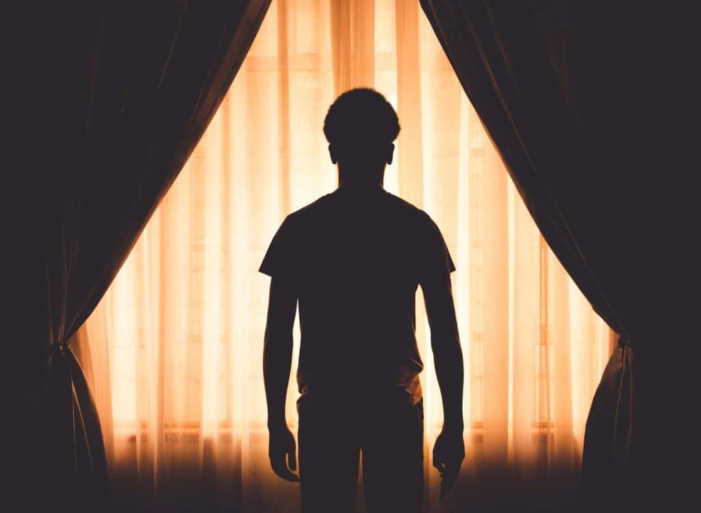 Silhueta de homem em janela com cortinas e janela iluminada