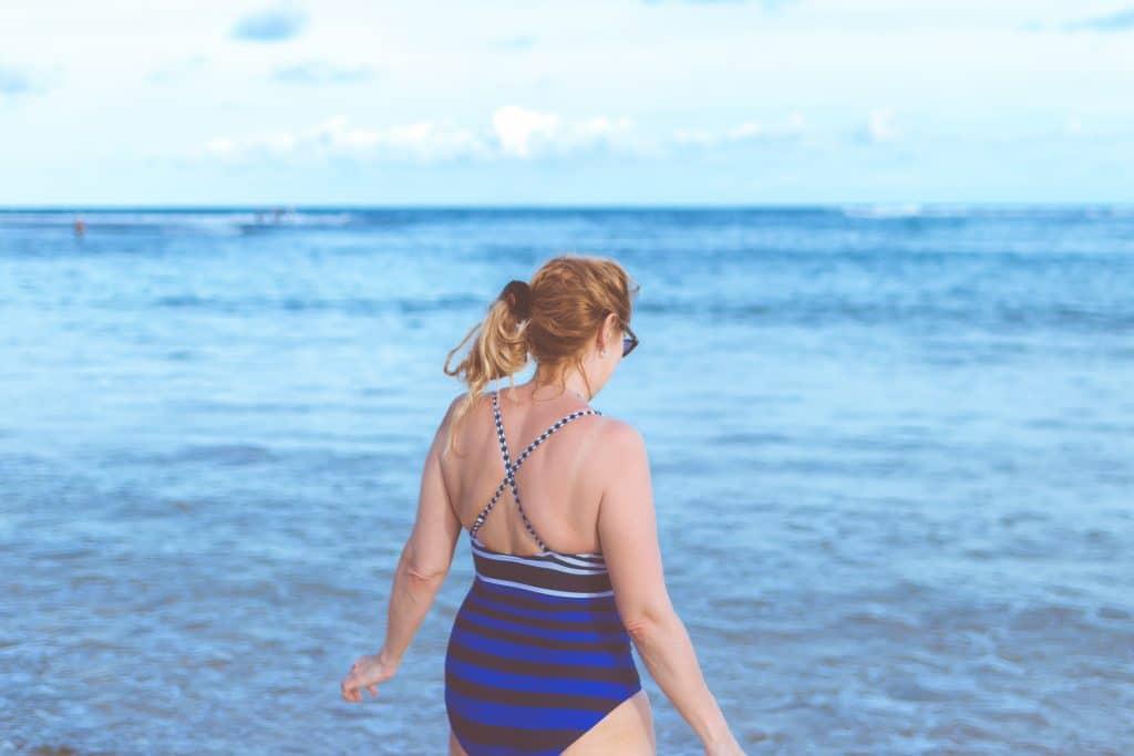 Mulher adulta usando maiô e com os cabelos presos de frente para a praia.