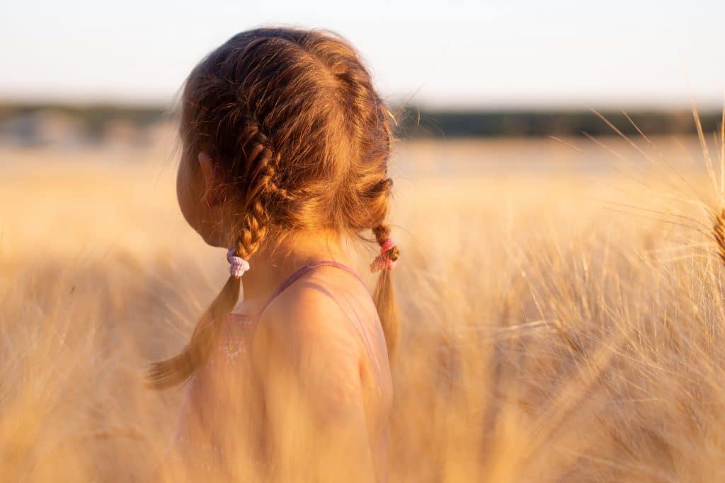 Criança menina de tranças no cabelo, olhando para trás em um campo, ao pôr do sol.
