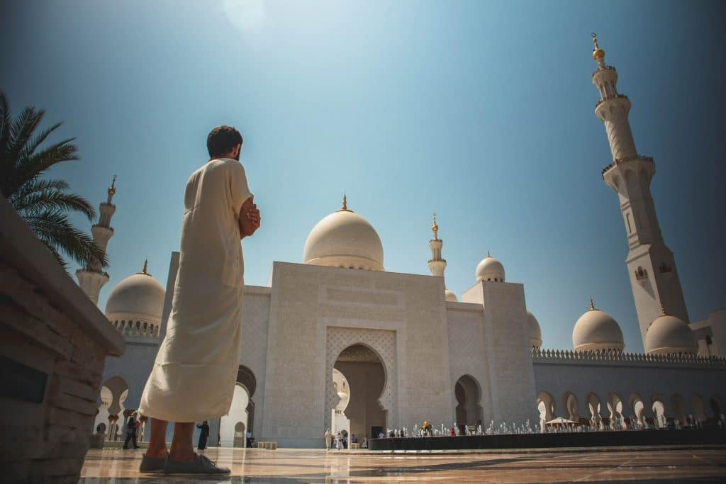 homem de pé perto da mesquita branca