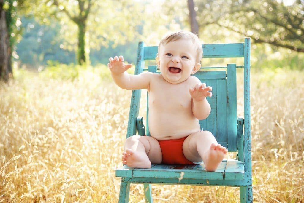 Criança sentada em uma cadeira que está no gramado