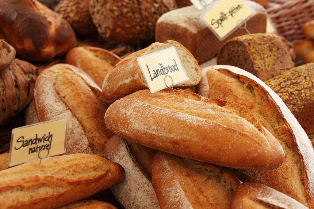 Vários tipos de pães espalhados sobre uma mesa.