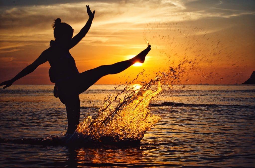 Silhueta de mulher chutando água do mar com sol ao fundo