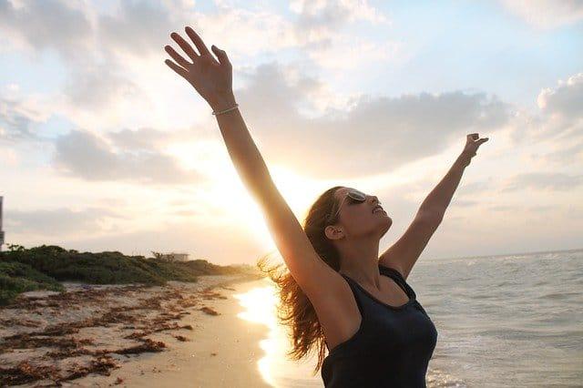 Mulher na beira do mar com braços abertos e óculos de sol com sol refletindo ao fundo