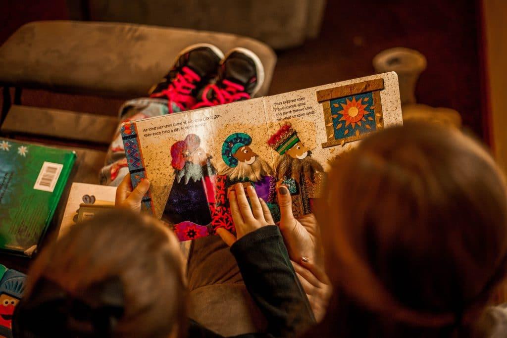 Duas crianças lendo livro no sofá
