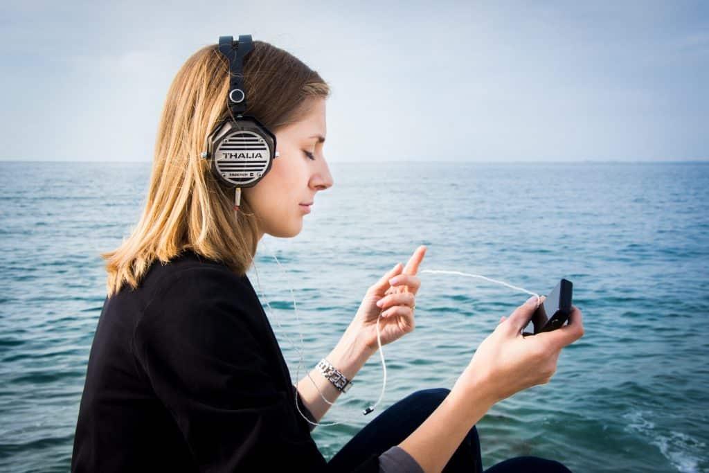 Mulher sentada ao lado de um mar ouvindo música no fone de ouvido