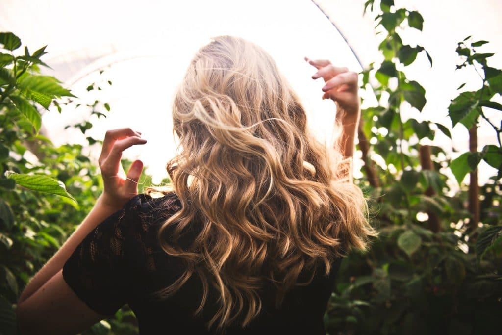 Mulher de cabelos ondulados de costas, em meio a uma estufa com plantas.