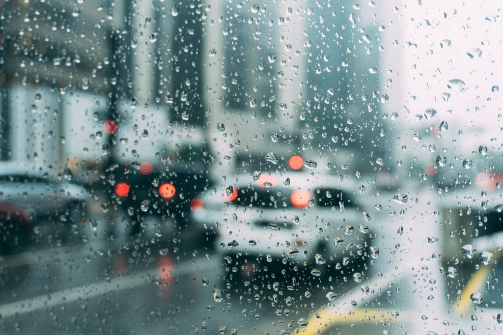 Janela de carro molhada com gotas de chuva, mostram carros parados em trânsito.