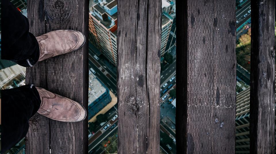 Pés usando sapato marrom em cima de uma placa de madeira. Uma sequência de placas de madeira segue em frente, com um espaço entre elas, como uma ponte. Entre os espaços, é possível ver uma cidade, e um cruzamento de duas avenidas, indicando que a pessoa esteja atravessando em um local muito alto.
