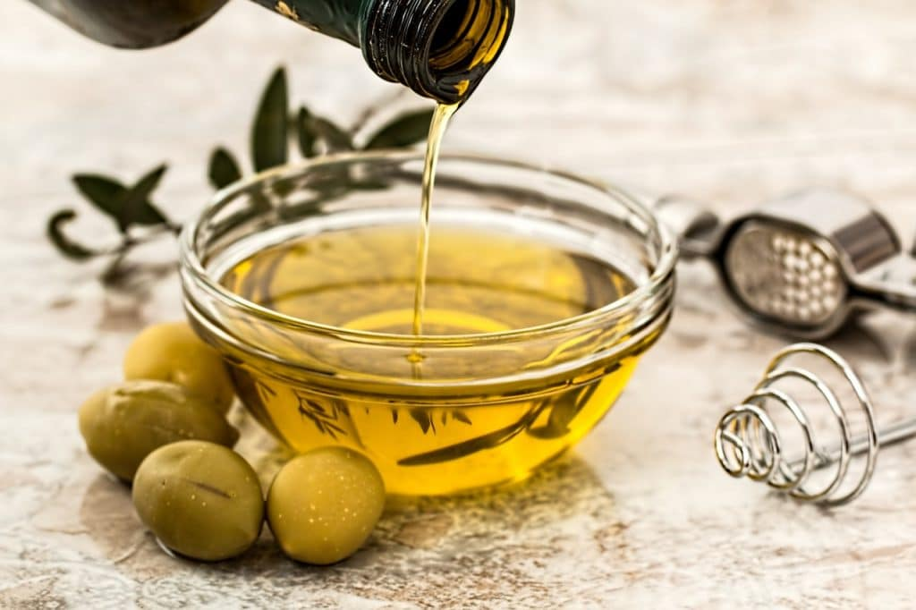 Azeite de oliva sendo despejado em um recipiente de vidro, cercado por azeitonas.
