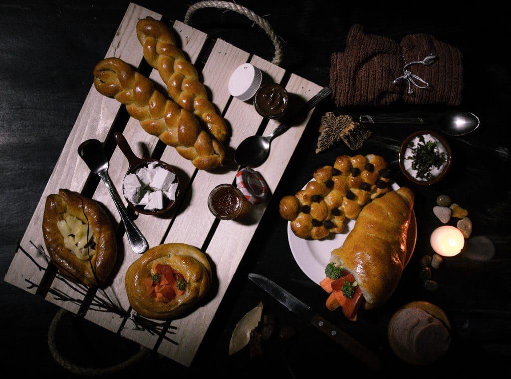 Bandeja de madeira e sobre ela alguns tipos de pães, doces e geleias. Ao lado mais alguns tipos de pães e outros elementos decorativos.