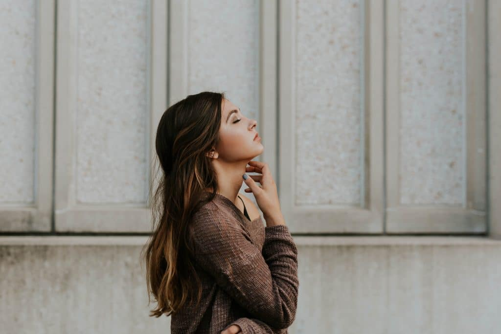 Mulher de perfil com olhos fechados e mão no pescoço