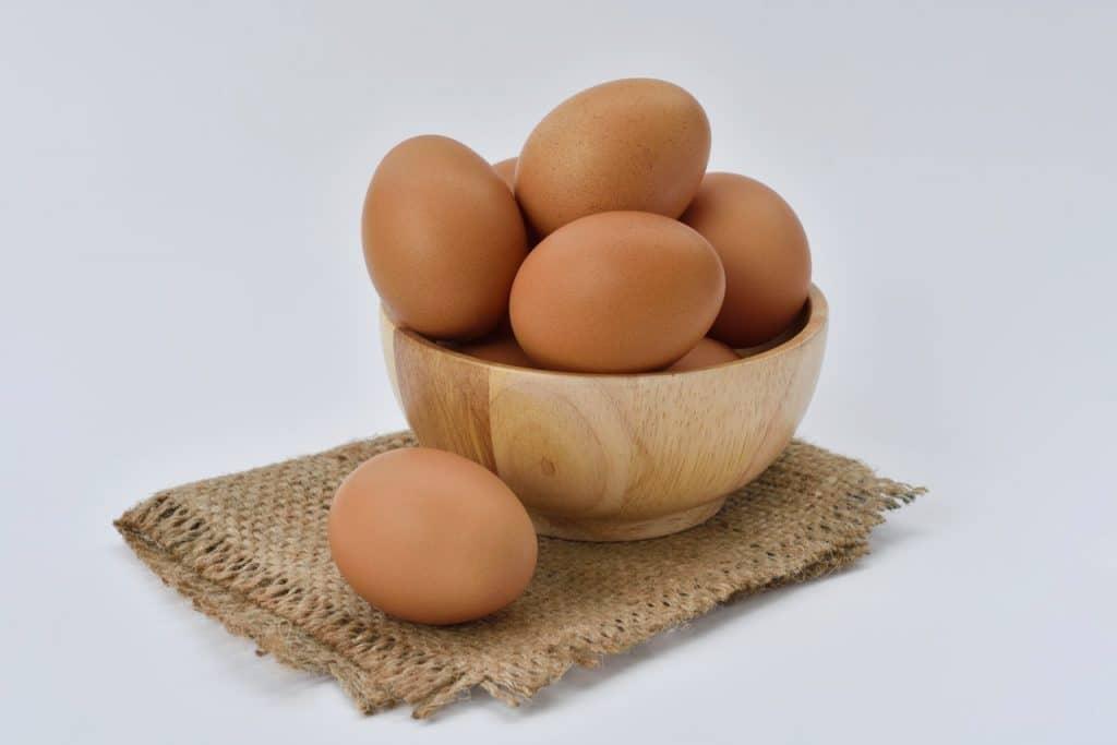 Ovos em uma cesta sobre uma pequena toalha.