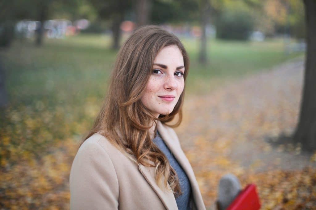 Mulher jovem de cabelos lisos e roupas de frio em um parque, no outono.