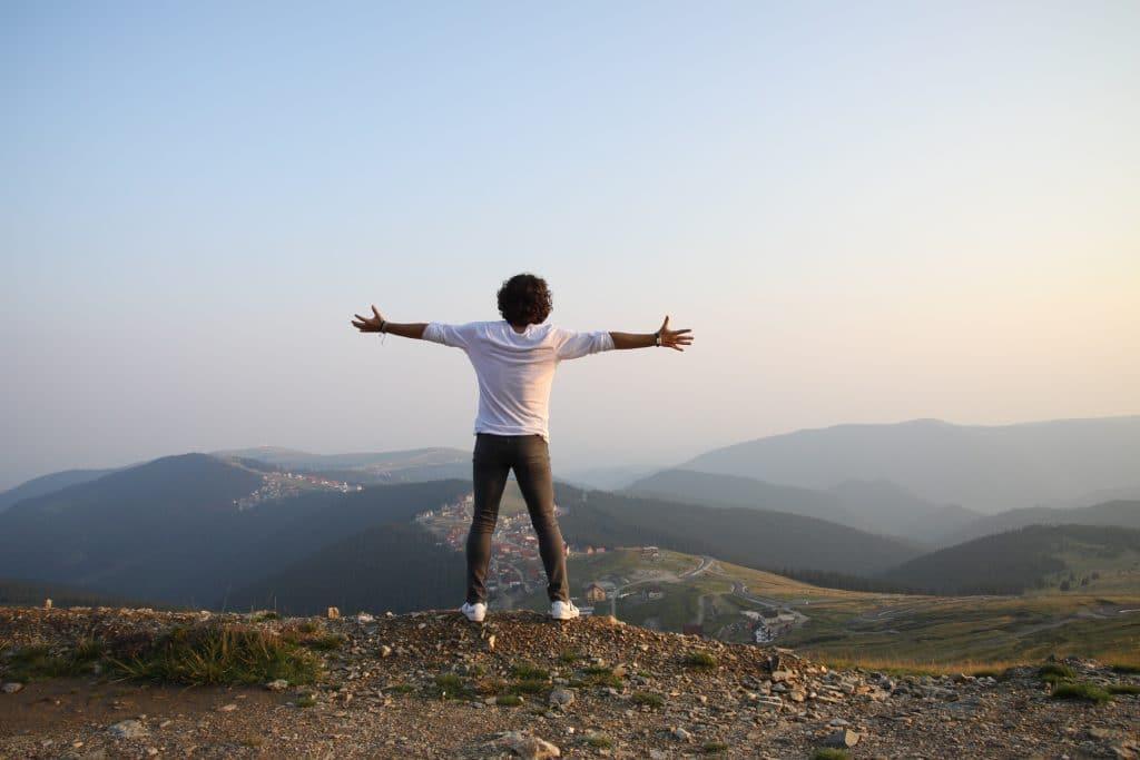 Homem com os braços abertos olhando para o horizonte com montanhas