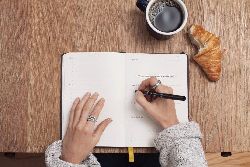 Mulher escrevendo em um caderno sobre uma mesa de madeira, ao lado de uma xícara de café e um croissant.