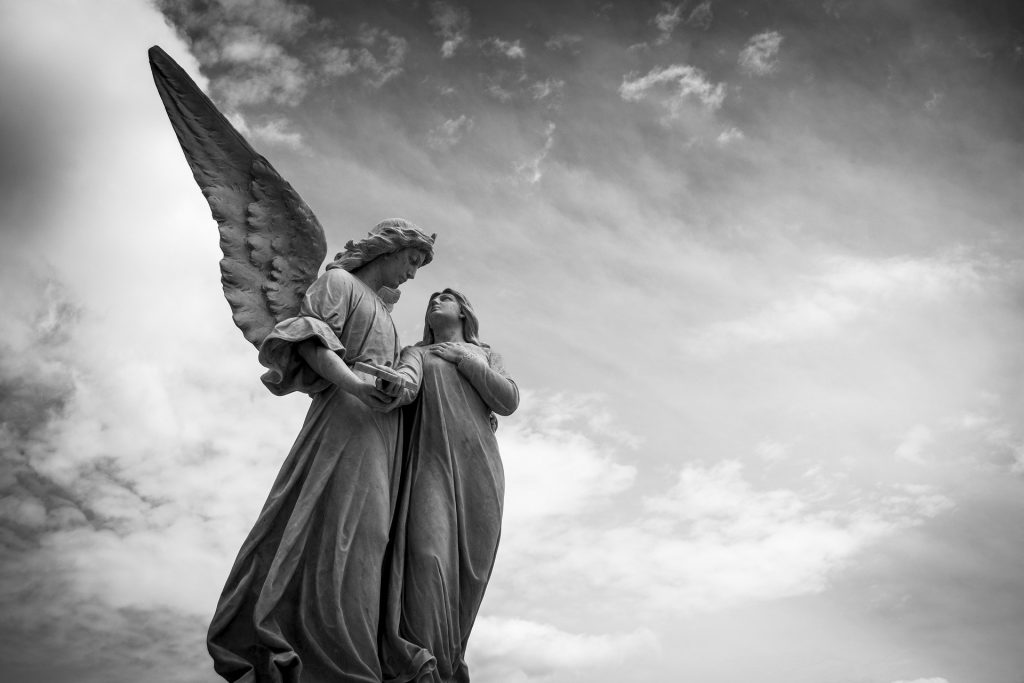 Imagem preto e brando de dois anjos, sendo que um deles está com asas. Ambos estão em um cemitério. Ao fundo o céu cinzento.
