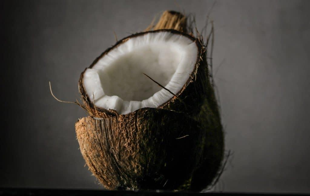 Coco cortado ao meio, com uma metade em cima da outra.