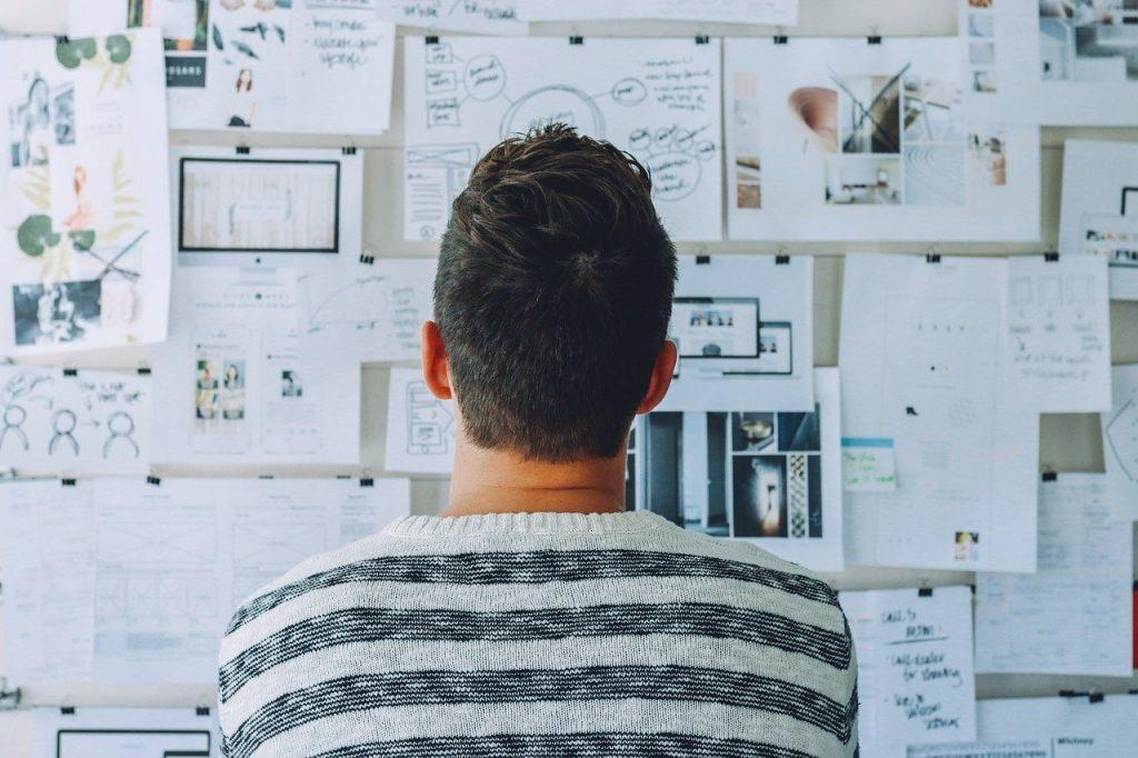 Homem de costas para a câmera, olhando para um painel em sua frente. Neste painel, estão presos vários papéis com textos, gráficos e imagens.