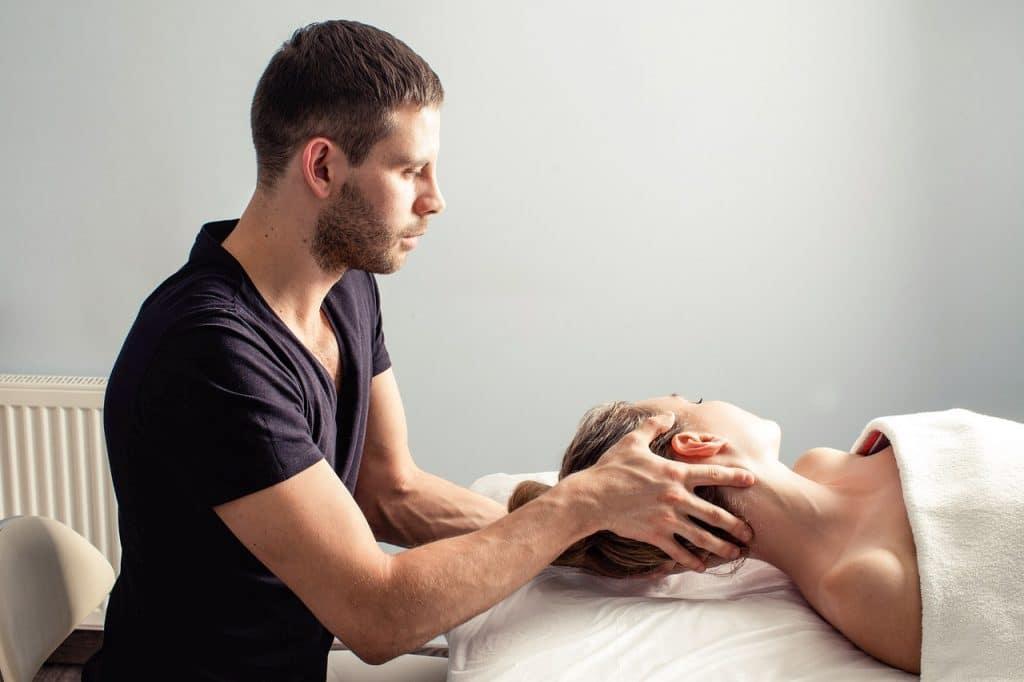 Homem terapeuta segurando a cabeça de uma paciente mulher, que está deitada e com uma toalha sobre o corpo.