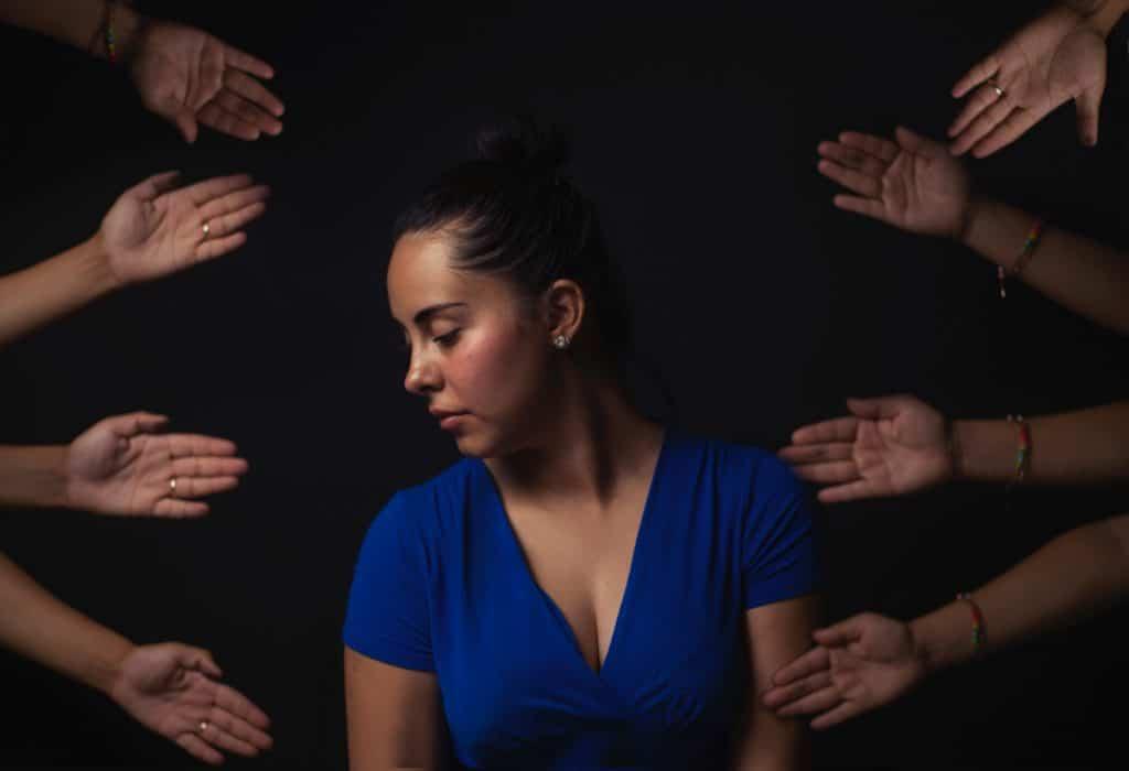 Mulher com a cabeça para o lado, olhando para baixo, em meio a várias mãos estendidas voltadas a ela.