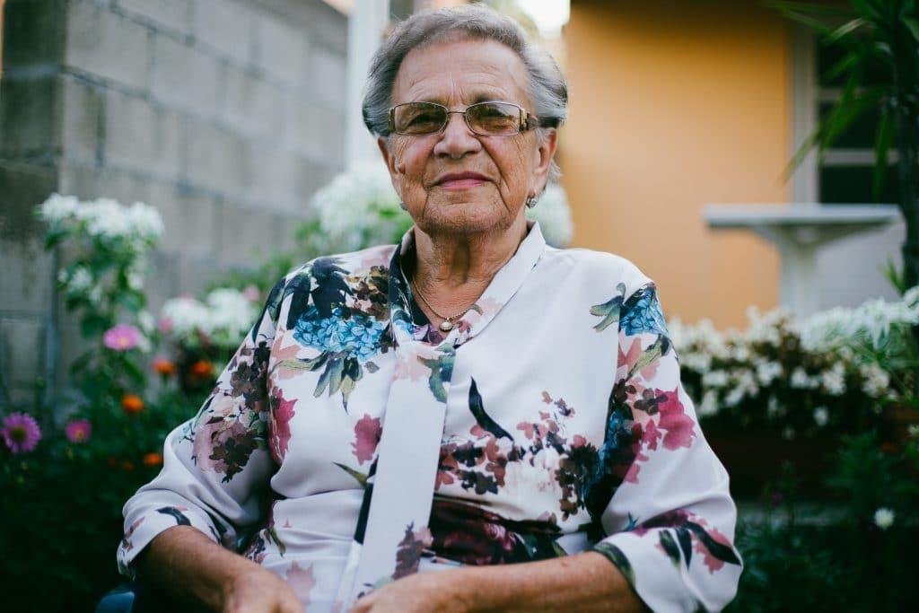Mulher idosa sentada em um quintal com flores, de óculos, com um leve sorriso no rosto.