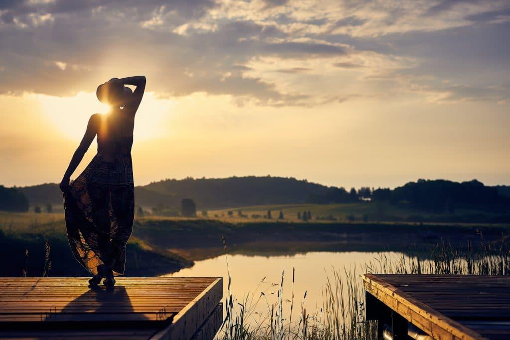 Mulher de costas em deck de madeira com luz do sol refletindo e paisagem de campo