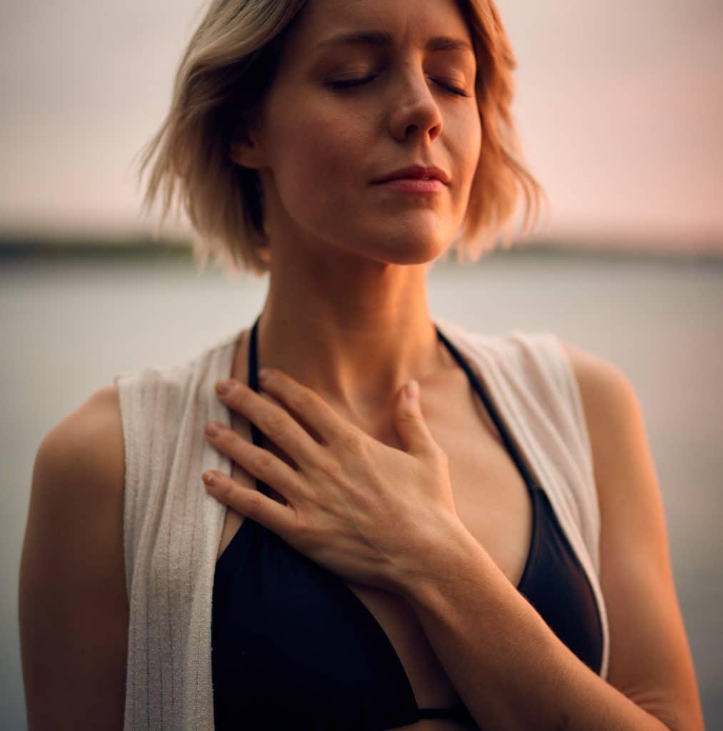 Mulher com os olhos fechados e com a mão a cima do peito