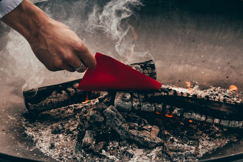 Mão jogando um pequeno pedaço de papel em uma fogueira.