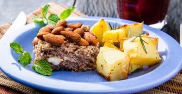 Prato azul com um pedaço de bolo de carne com nozes e batata assada.