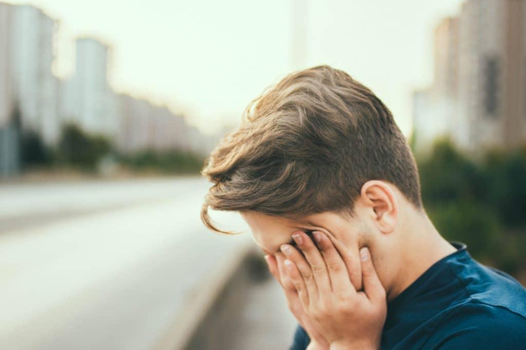 Pessoa na rua de uma cidade, cansada, esfregando os olhos com as mãos.