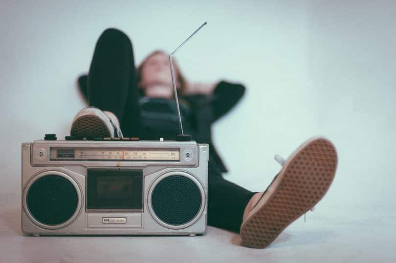 Pessoa deitada no chão com o pé apoiando em um rádio antigo