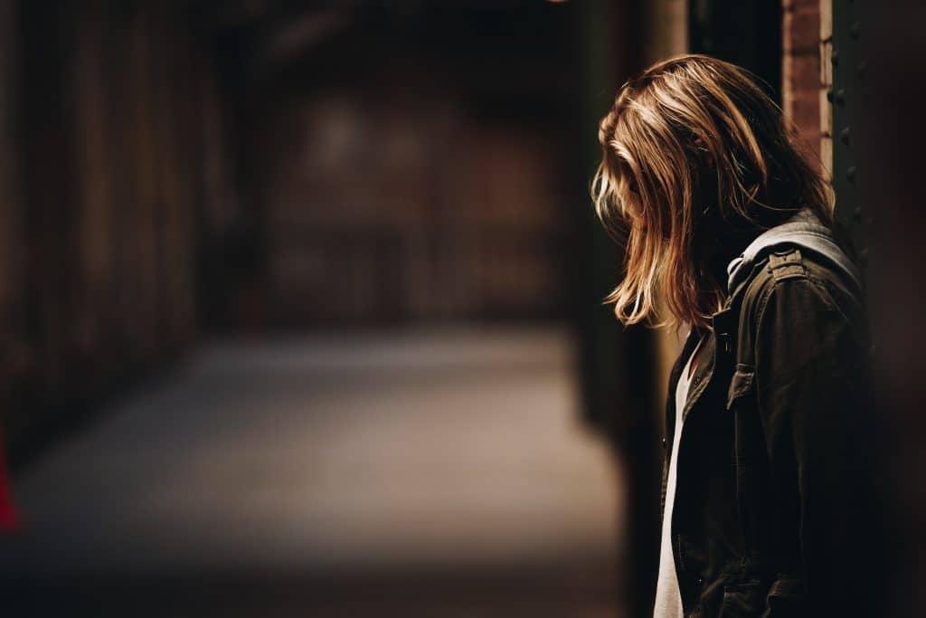 Mulher de lado encostada em parede com cabeça abaixada