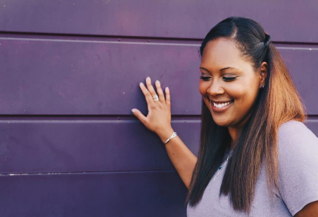 Mulher adulta sorrindo enquanto olha para baixo e apoia a mão sobre uma parede.